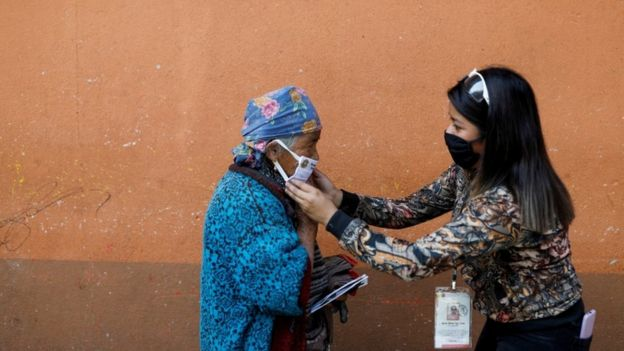A municipal worker adjusts a protective face mask on a woman on the street amid the outbreak of the coronavirus disease (COVID-19), in Totonicapan, Guatemala April 19, 2020