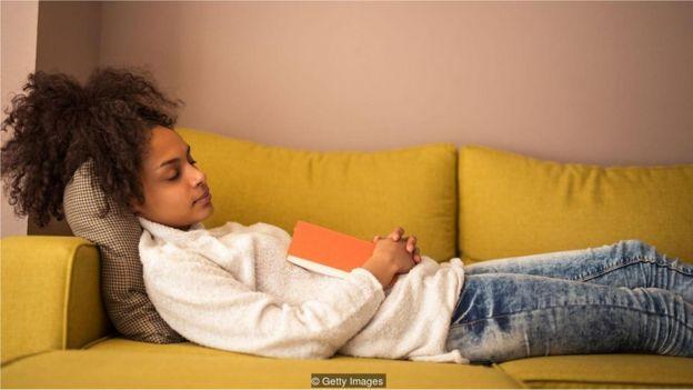 Jovem dormindo com livro