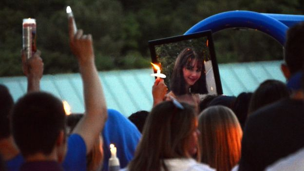 A photograph of Bianca is held at a vigil, where candles are seen in the air