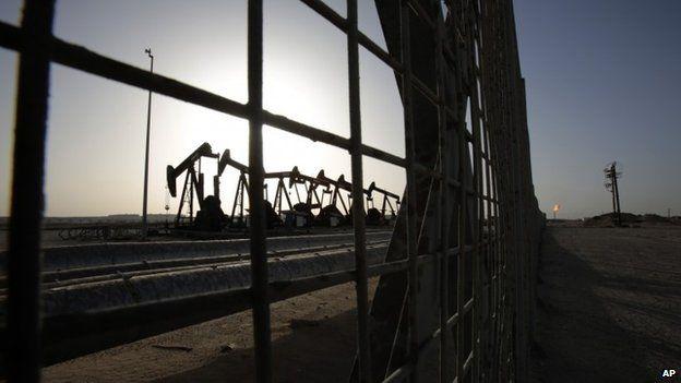 Oil pumps work in the desert oil fields of Sakhir, Bahrain