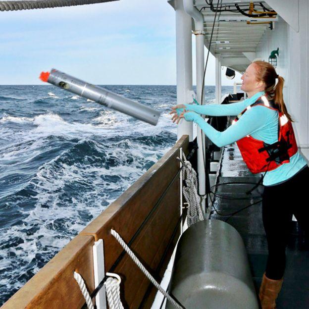 Jessica Crance a bordo de una embarcación lanzando una sonoboya al mar