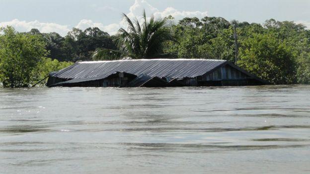 Casa com água na altura do teto no rio Solimões em 2012