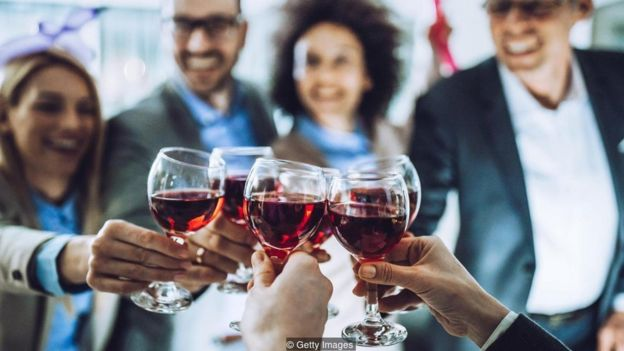 Quatro pessoas brindam com taças de vinho
