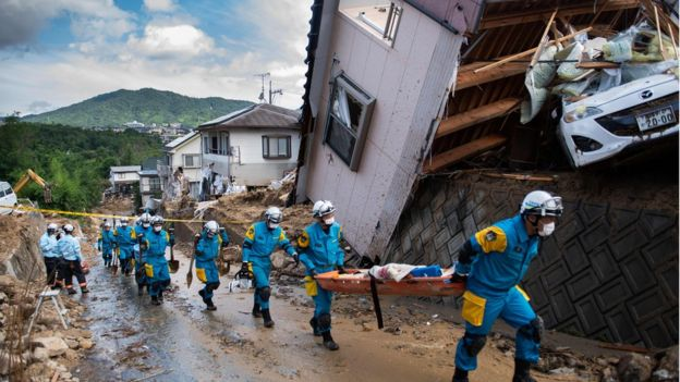 Police arrive to clear debris scattered on a street in a flood-hit area in Japan's Hiroshima prefecture 9 July 2018