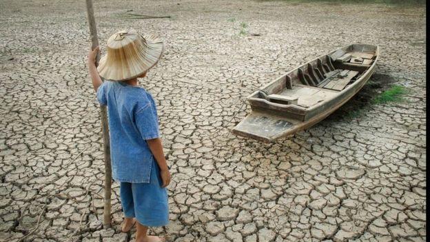 Menino diante de barco sobre solo rachado pela seca