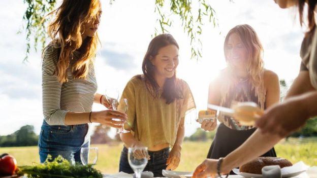 Cuatro chicas comiendo y bebiendo.