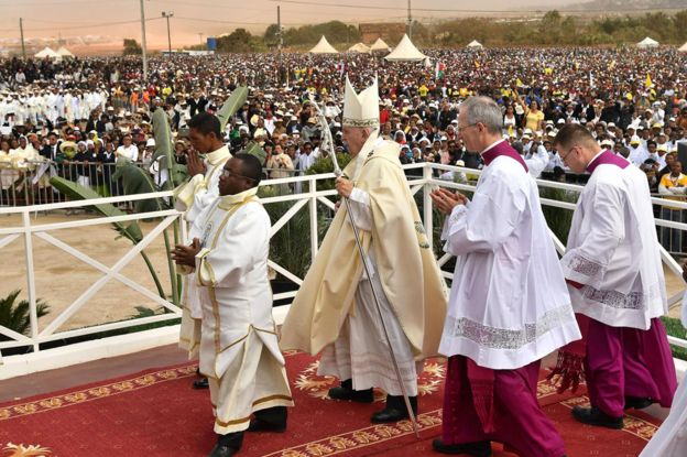 Pope walking on alter in front of crowd in Madagascar
