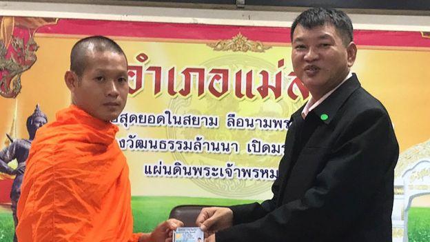 Wild Boar soccer team coach-turned-Buddhist monk Ekapol Chantawong (L) as he receives Thai citizen ID card from Mae Sai District Chief Somsak Kanakham (R)