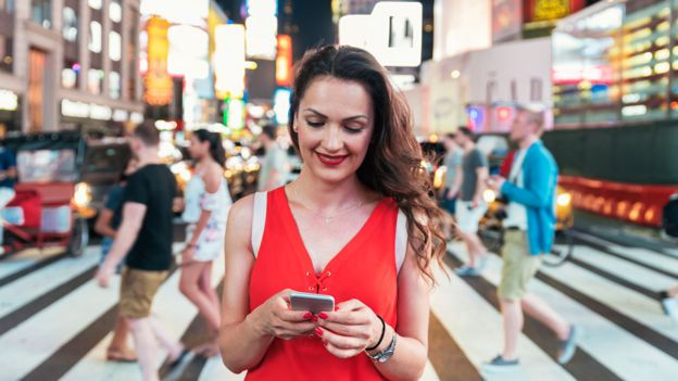 Una mujer mira su celular en Times Square, Nueva York