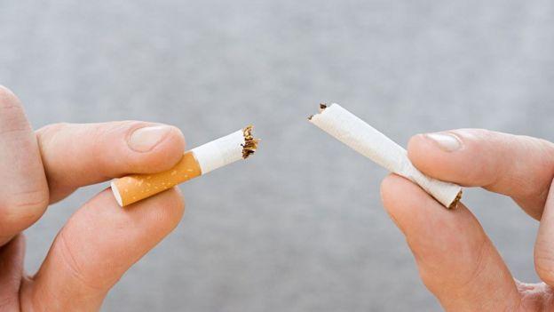 Pessoa partindo cigarro no meio