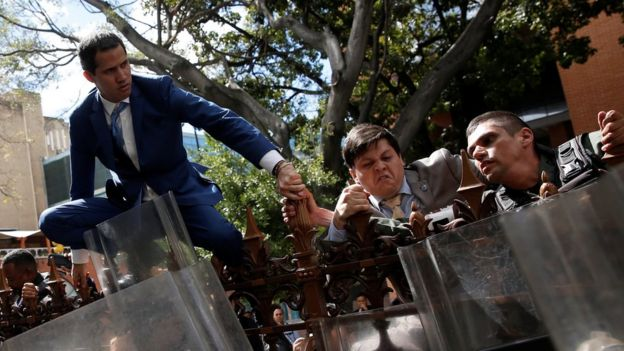 Juan Guaidó trepa una verja.