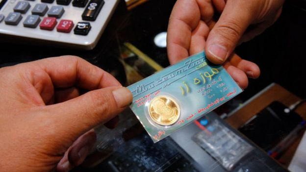 An Iranian shopkeeper sells a gold coin at a shop in Tehran (5 August 2018)