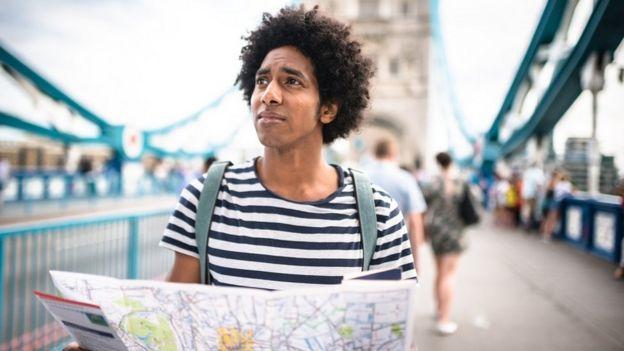 Un hombre joven sosteniendo un mapa en Tower Bridge, Londres.
