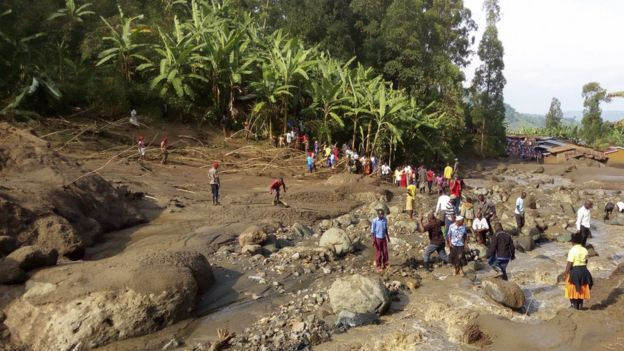 People gather at the scene of a landslide in Bududa area in eastern Uganda,