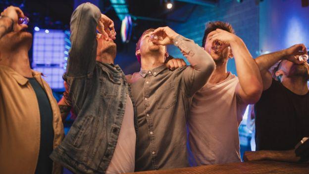 Un grupo de hombres tomando tragos.