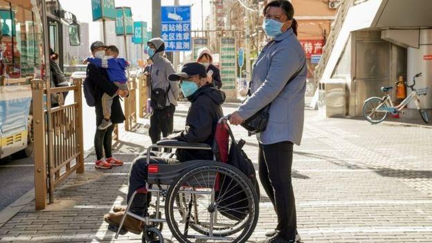 صينيون يرتدون أقنعة واقية وينتظرون الحافلة