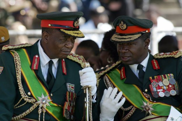 Zimbabwe's Army commander General Constantine Chiwenga (L) chats with commander of the Zimbabwe National Army, Lieutenant-General Phillip Valerio Sibanda, during the country's 28th year of independence celebration in Harare on April 18, 2008.