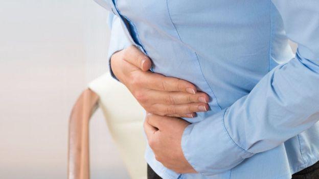 Una mujer se toca el estómago