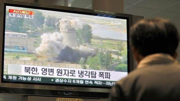 一名韩国人看着销毁朝鲜宁边冷却塔的录像
