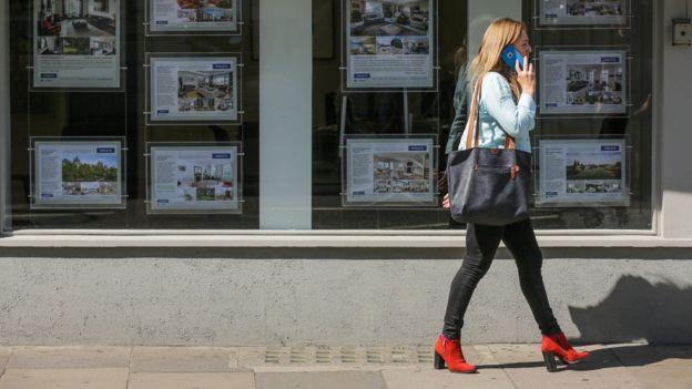 Woman walks past estate agent window