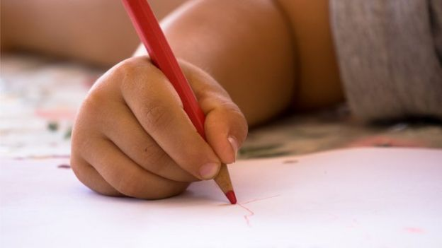 A boy doodling on a paper with a red crayon