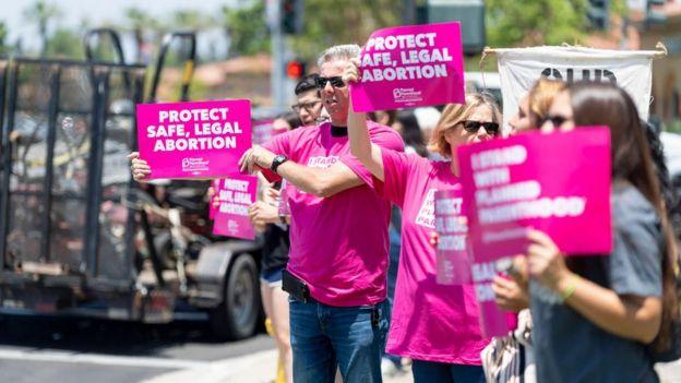 Manifestantes sostienen carteles en defensa del aborto legal y seguro en en Irvine, California en junio de 2019.