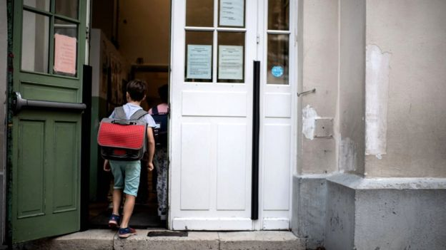 A boy enters in his classroom at the Chaptal elementary school in Paris, 2 September 2019