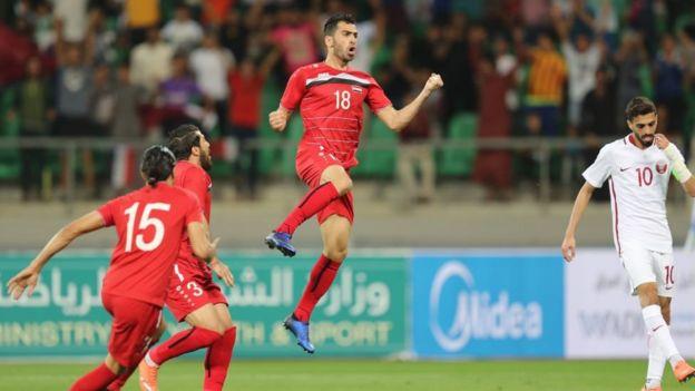 Syrians celebrate a goal