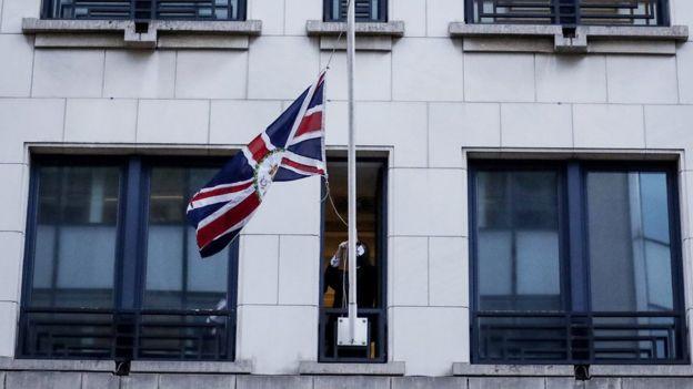 İngiltere'nin Avrupa Birliği Daimi Temsilcisi Tim Barrow, ülkesinin bayrağını indiriyor