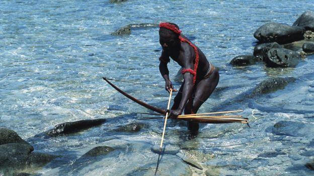Un jarawa pescando con arco y flecha