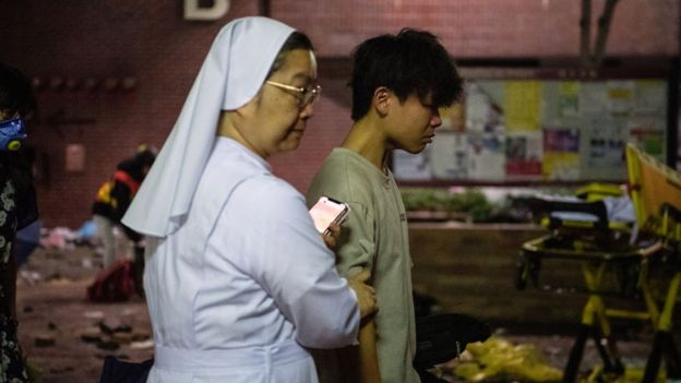 A nun leading a protester out of PolyU