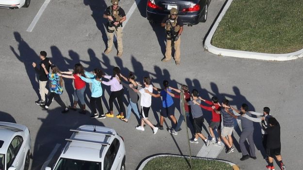 People are brought out of the Marjory Stoneman Douglas High School after a shooting at the school that reportedly killed and injured multiple people on February 14, 2018 in Parkland, Florida.