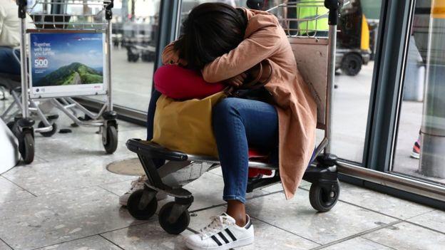 A woman sleeps on a luggage trolley at Heathrow Terminal 5