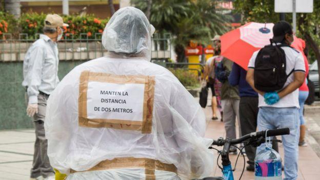 Una persona con un cartel en el que pide que se respete la distancia
