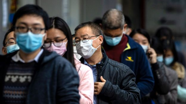 People queue outside a pharmacy as they won the lottery to buy protective masks, in Guangzhou, China, 13 February 2020.