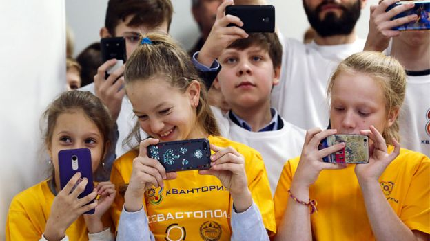 Russian children using mobiles in a science park