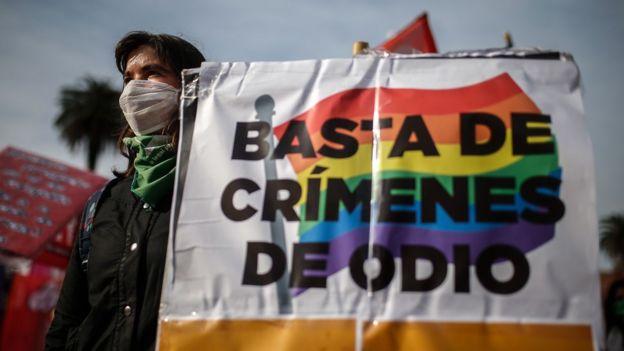 Mujer con una pancarta que dice Basta de crímenes de odio