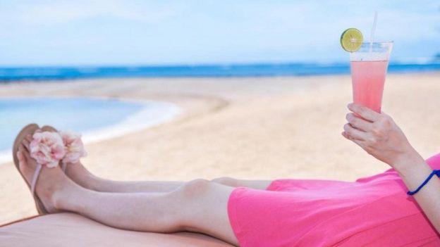 Mulher tomando drink na praia