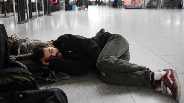 boy sleeping on the airport floor