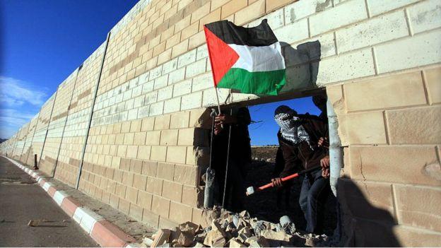 Palestinos en un boquete del muro