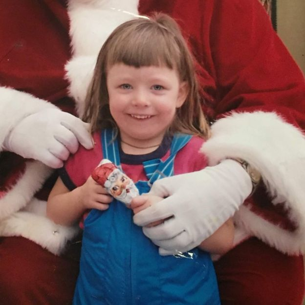 A young Ashley at around 7-years-old standing in front of a Santa Claus