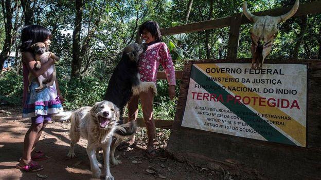 Dos pequeñas indígenas juegan con sus perros frente a un letrero de la FUNAI que anuncia la protección de un terreno guaraní en Brasil