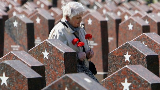 A woman walks past graves of soldiers killed during WW2 at a cemetery in central Moscow (8 May 2006)