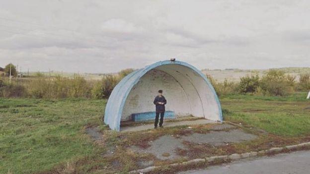 Hombre en una parada de autobús en un sitio remoto en Rusia