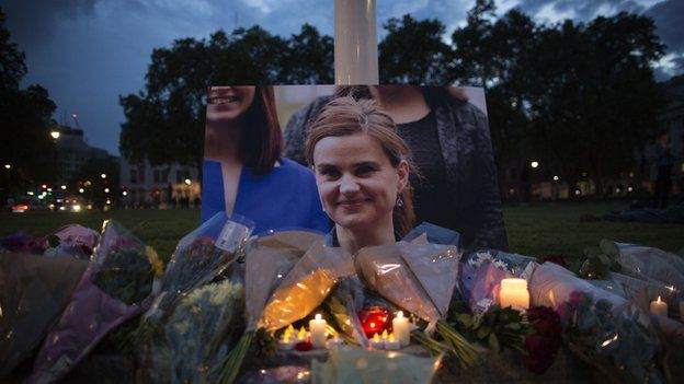 Flowers surround a picture of Jo Cox during a vigil in Parliament Square on 16 June 2016