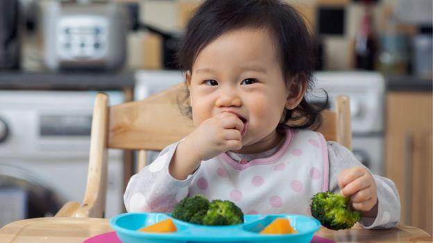 Bebé comiendo verduras con la mano