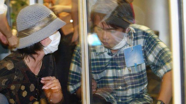 مرد در کنار دیوار شیشهای در فرودگاه هانوی، پس از بازگشت از چین در دوران همهگیری ویروس سارس