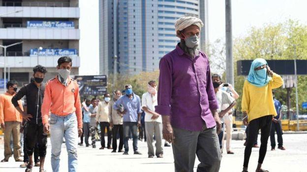 Pessoas na Índia fazem fila diante de uma cozinha comunitária mantendo uma distância segura