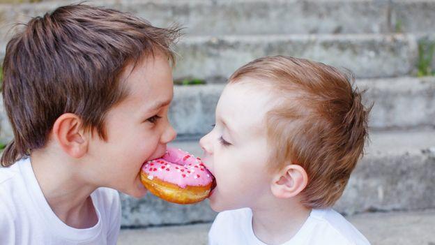Niños compartiendo un dulce.