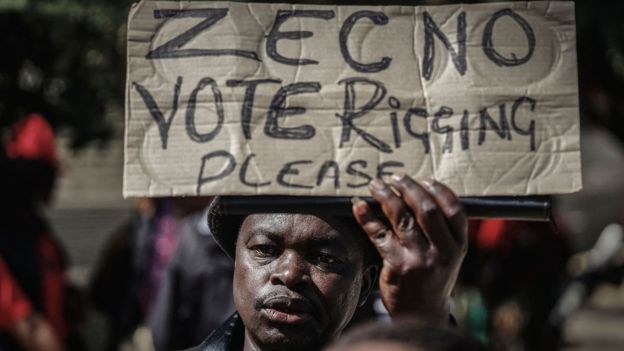 A protester waves a placard demanding transparency in Bulawayo, Zimbabwe 13 July 2018